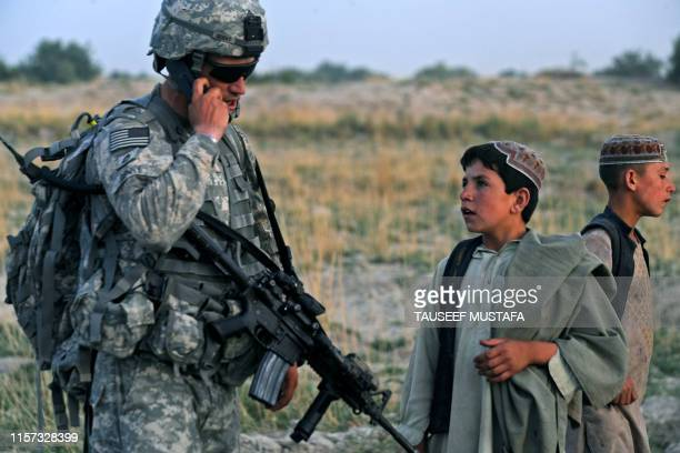 Afghan children look on as US soldiers from Bravo Troop 171 CAV Forward Operating Base Wallakan SFC Denny takes part in a patrol in the village of...