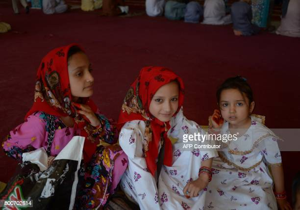 Afghan children look on during Eid alFitr prayers in the courtyard of Hazrat Ali shrine or Blue Mosque in MazariSharif on June 25 2017 / AFP PHOTO /...