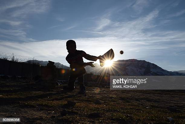 TOPSHOT Afghan children play cricket during sunset near of the ruined Darul Aman Palace in Kabul on January 82016 Celebratory gunfire has killed a...
