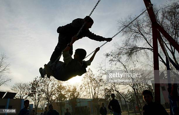 Afghan children play on the new swings at the Khar Khana Kindergarten playground on January 20 2003 in Kabul Afghanistan A ceremony marked the...