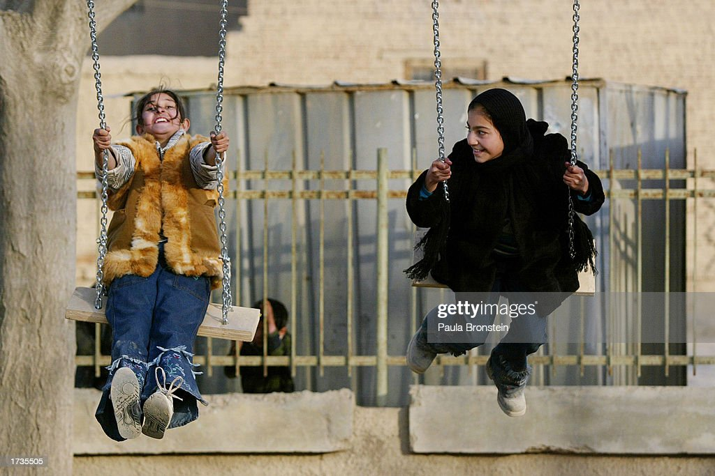 Afghan children play on the new swings at the Khar Khana Kindergarten playground on January 20, 2003 in Kabul, Afghanistan. A ceremony marked the completion of the $22,000 refurbishment project by the British International Security Assistance Force (ISAF), 51 Highland Regiment. The project involved new classrooms for the school and the construction of a new playground.