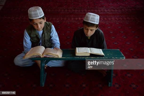 TOPSHOT Afghan children read the Koran at a madrasa during the holy month of Ramadan in Ghazni on June 13 2017 Muslims throughout the world are...
