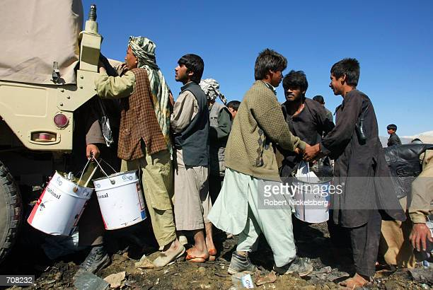 Afghan children root through refuse dumped by the US military and pull out whatever can be reused or sold off April 10 2002 at a landfill near the...