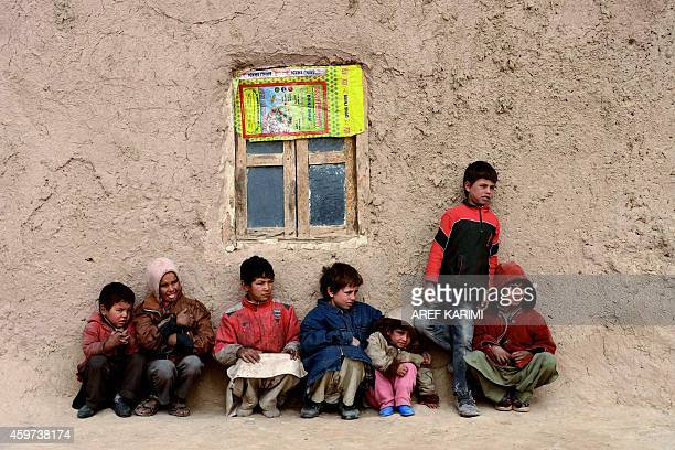 Afghan children sit near their home in Herat on November 30 2014 As winter sets in across Central Asia many Afghans struggle to provide adequate food...