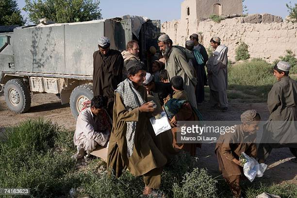 Afghan Children storm a box containing candies and biscuits delivered by British Soldiers from the Grenadier Guards on May 14 2007 in Southern...