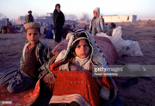 Afghan children wake up after sleeping outside in nearly freezing temperatures February 24 2001 at the Minarets refugee camp in Herat Afghanistan...