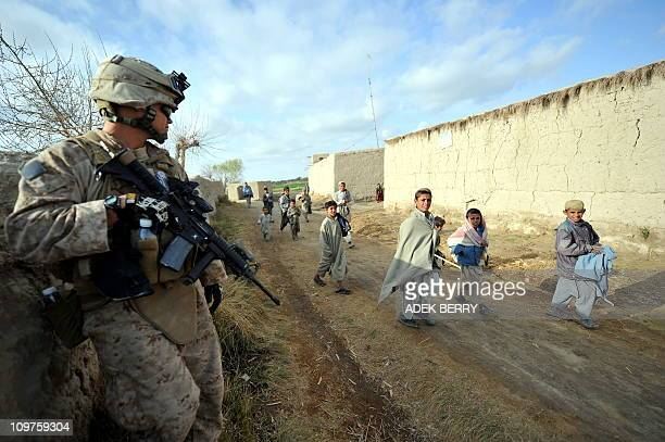 Afghan children walk past a US Marine of the 2nd Batallion 1st Marines Weapons Company during a joint patrol with Afghanistan National Army soldiers...