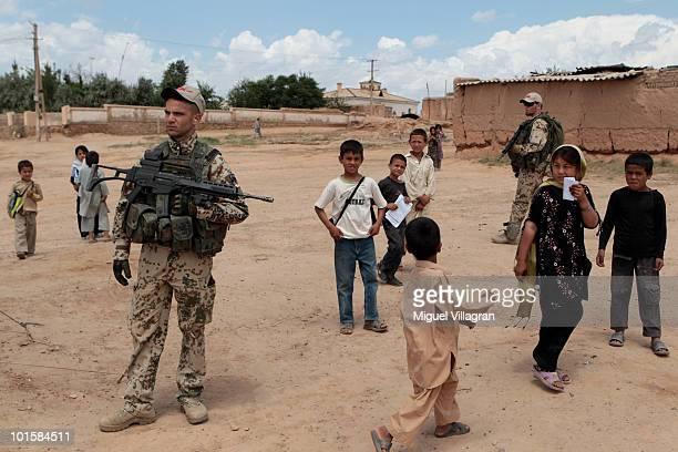 Afghan children walk past German soldiers on June 3 2010 in Shir Khan Afghanistan Germany has more than 4500 military forces in Afghanistan as part...