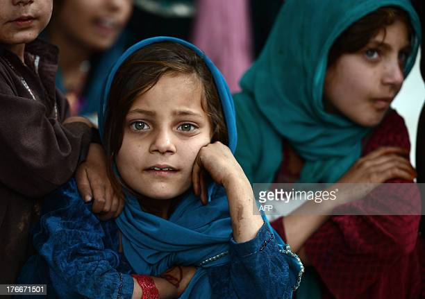 Afghan children watch a performance from the Mobile Mini Circus for Children during a show in Paghman district on the outskirts of Kabul on August...