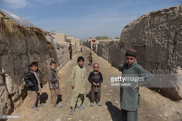 Afghan children watch Afghan National Army soldiers in DandeGhori district in Baghlan province on March 15 following weeks of heavy battles to...