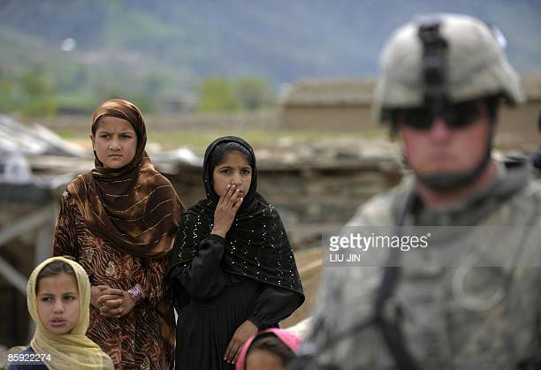 Afghan children watch US Army soldiers patrolling in Naray, in the eastern Kunar province on April 13, 2009. US President Barack Obama, unveiling his...