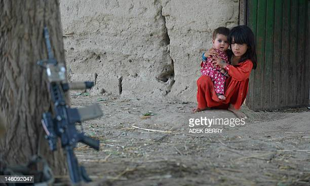 Afghan children watch US Marines from Baker Company of the1st battalion 7th Marines Regiment while conducting a night patrol in Sangin on June 9 2012...