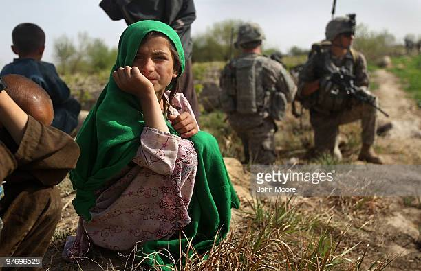 Afghan children watch US soldiers who had stopped at their family's farm after a nearby firefight with Taliban insurgents on March 14 2010 at...