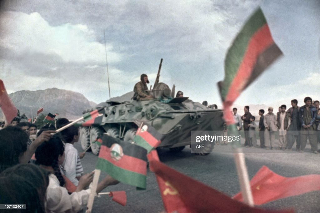 Afghan children wave Afghan and Soviet flags 15 May 1988 near Kabul as Russian troops aboard a BRDM, Soviet-made armoured Combat Reconnaissance Patrol Vehicle, began their withdrawal from war-torn Afghanistan. The Soviet war in Afghanistan, also known as the Soviet-Afghan War, was a nine-year conflict involving Soviet forces supporting the Marxist People's Democratic Party of Afghanistan (PDPA) government against the Mujahideen resistance. The initial Soviet deployment of the 40th Army in Afghanistan began on August 7, 1978. The final troop withdrawal began on May 15, 1988, and ended on February 15, 1989.