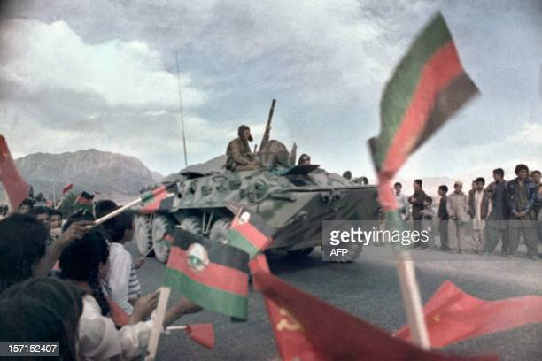 Afghan children wave Afghan and Soviet flags 15 May 1988 near Kabul as Russian troops aboard a BRDM Sovietmade armoured Combat Reconnaissance Patrol...