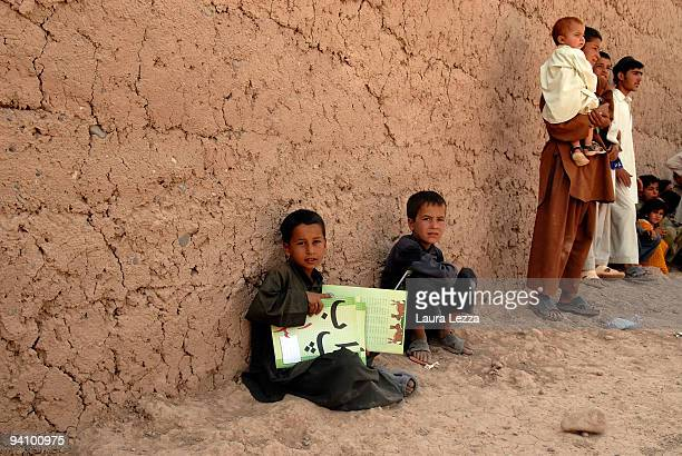 Afghan children with pencils and notebooks outside a school after the visit of Italian soldiers of the Folgore Parachute Brigade on September 16 2009...