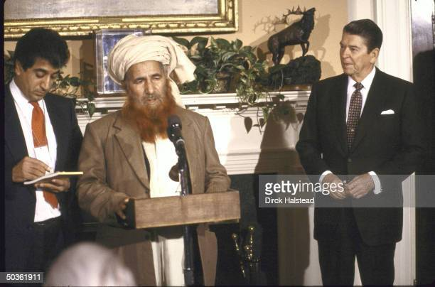 Afghan Chrmn of Islamic Union of Mujahedeen Mohammed Younis Khalis speaking at podium with Pres Ronald W Reagan standing by