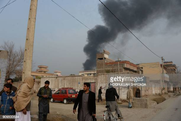 TOPSHOT Afghan civilians gather on a street next to a plume of smoke coming from the area around an office of the British charity Save the Children...