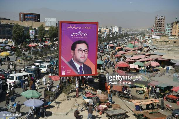 Afghan commuters and pedestrians are seen along road as a billboard with a poster of candidate Haji Hafizullah Jalili is seen near a busy market...