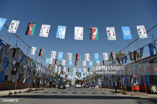 Afghan commuters drive as posters of candidate Ahamd Tamin Jurat are installed during the parliamentary election campaign in Kabul on October 2 2018...
