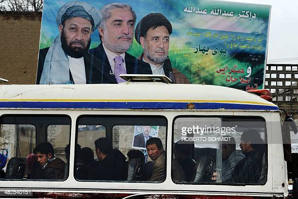Afghan commuters look out of a bus window next to a political billboard at a bus stop in Kabul on April 4 2014 Some 12 million Afghans will go to the...