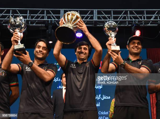 Afghan cricket captain Asghar Stanikzai and teammates Mohammed Nabi and Rashid Khan pose for photographs during an event to celebrate the Afghan...