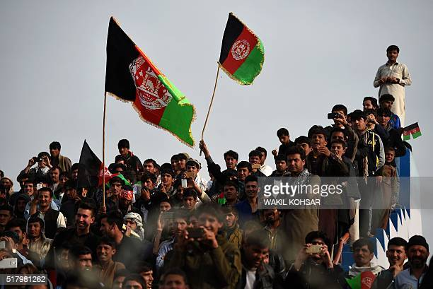 Afghan cricket fans cheer and wave the national flag as they welcome the country's cricket team home at the Cricket Board Stadium in Kabul on March...