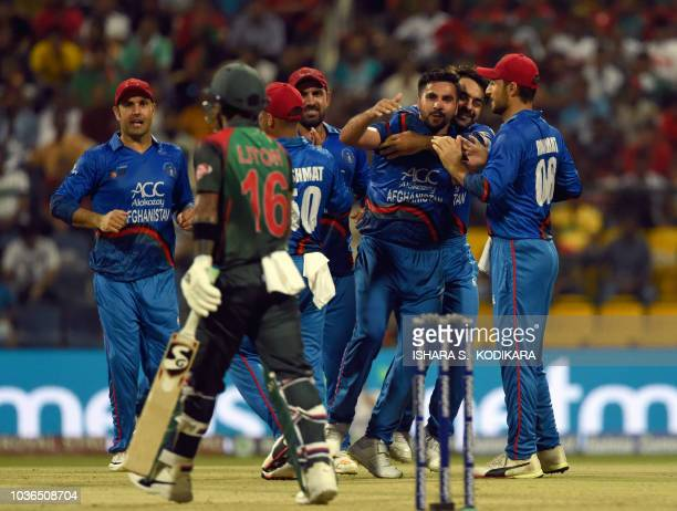 Afghan cricketer Aftab Alam celebrates with teammates after he dismissed Bangladesh batsman Liton Das during the one day international Asia Cup...
