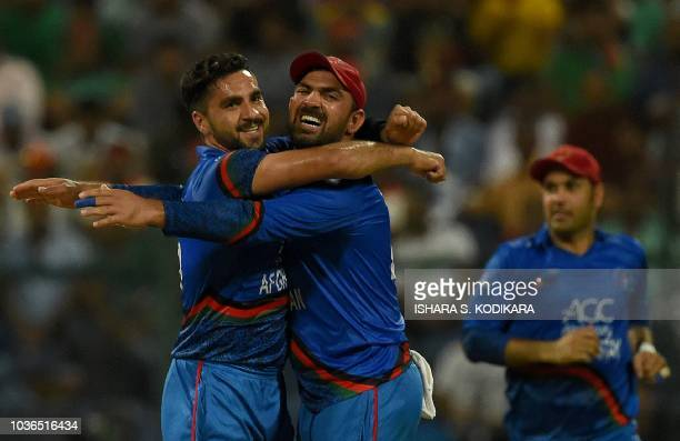 Afghan cricketer Aftab Alam celebrates with teammates after he dismissed unseen Bangladesh batsman Liton Das during the one day international Asia...