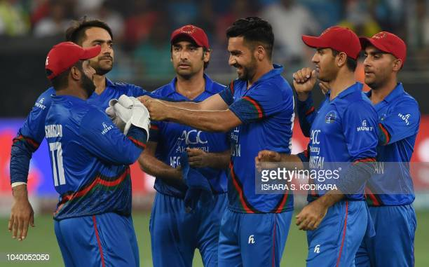 Afghan cricketer Aftab Alam celebrates with teammates after he dismissed unseen Indian batsman Manish Pandey after they collided with each other...