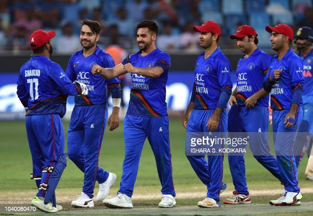 Afghan cricketer Aftab Alam celebrates with teammates after he dismissed unseen Indian batsman Deepak Chahar during the one day international Asia...