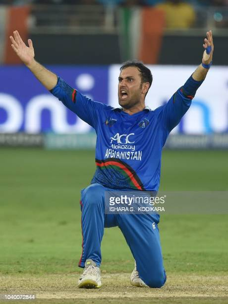 Afghan cricketer Mohammad Nabi celebrates after he dismissed unseen dismissed Indian batsman Dinesh Karthik during the one day international Asia Cup...