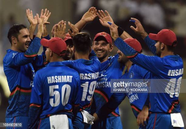 Afghan cricketer Mohammad Nabi celebrates with teammates after he dismissed Sri Lanka's cricket team captain Angelo Mathews during the one day...