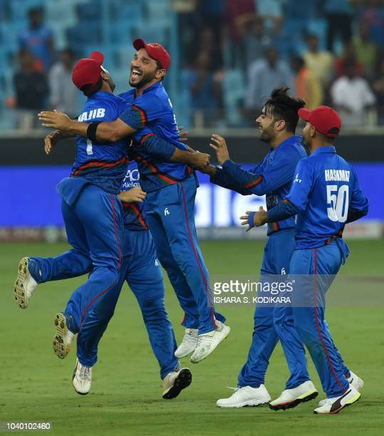 Afghan cricketer Rashid Khan celebrates with teammate after the match during the one day international Asia Cup cricket match between Afghanistan and...