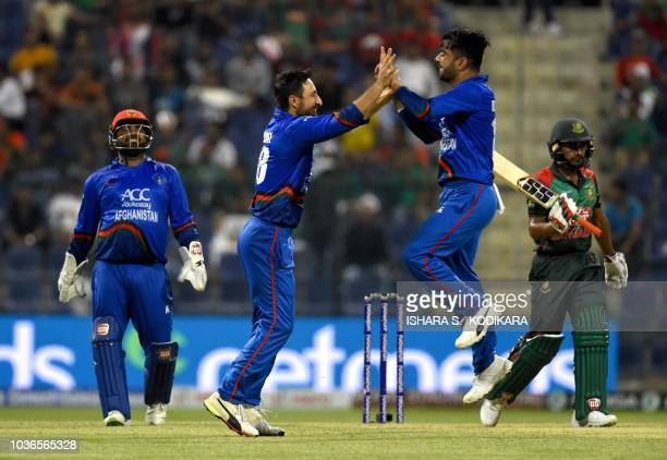 Afghan cricketer Rashid Khan celebrates with teammate Rahmat Shah and wicketkeeper Mohammad Shahzad after he dismissed Bangladesh batsman Mehidy...