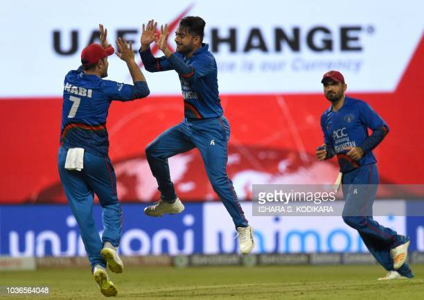 Afghan cricketer Rashid Khan celebrates with teammates after he dismissed unseen Bangladesh batsman Mohammad Mahmudullah during the one day...