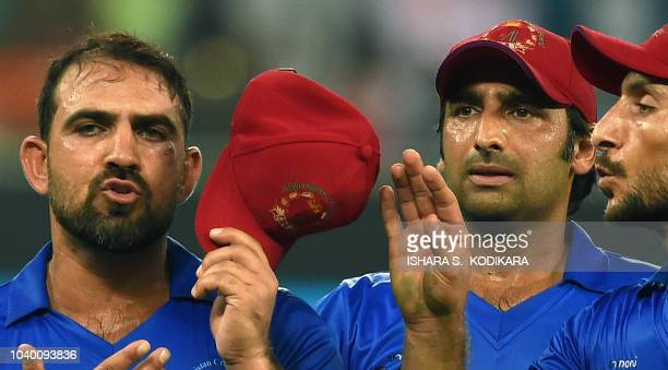 Afghan cricketer Samiullah Shenwari reacts as he leaves the field after getting injured during the one day international Asia Cup cricket match...