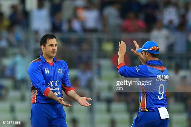 Afghan cricketers celebrate after the dismissal of Bangladesh's Mahmudullah during the first one day international cricket match between Bangladesh...