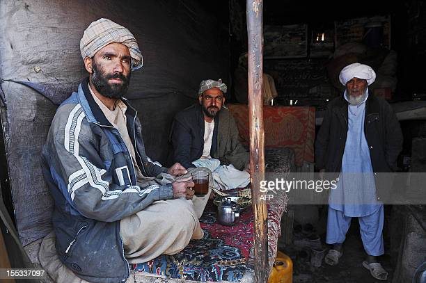 Afghan customers drinks sweet tea and eats bread a traditional Afghanistan breakfast in a tea house in Herat on November 3 2012 The wartorn country...