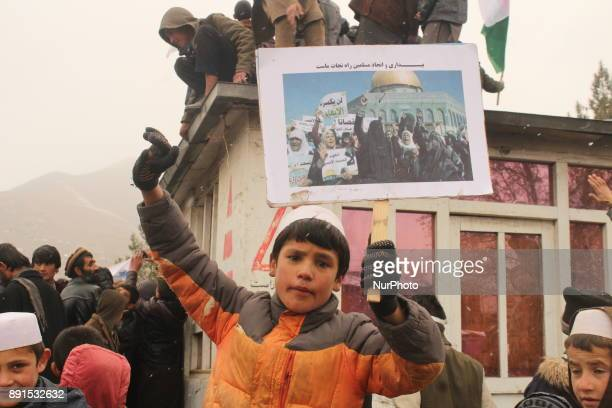 Afghan demonstrators hold placards during a protest against the US and Israel in Badakhshan province on 13 December 2017 Afghans are demonstrating...