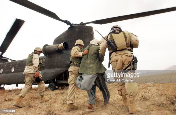 Afghan detainees are walked to a Chinook helicopter for transport by Special Operation Forces after a joint village raid between US Special Forces...
