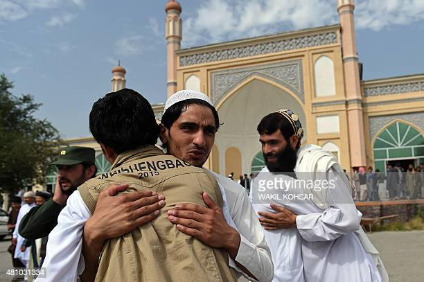 Afghan devotees greet each other after offering prayers at the start of the Eid alFitr holiday which marks the end of Ramadan at the Eid Gah Mosque...