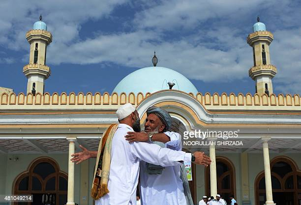 Afghan devotees greet each other after offering prayers at the start of the Eid alFitr holiday which marks the end of Ramadan on the outskirts of...