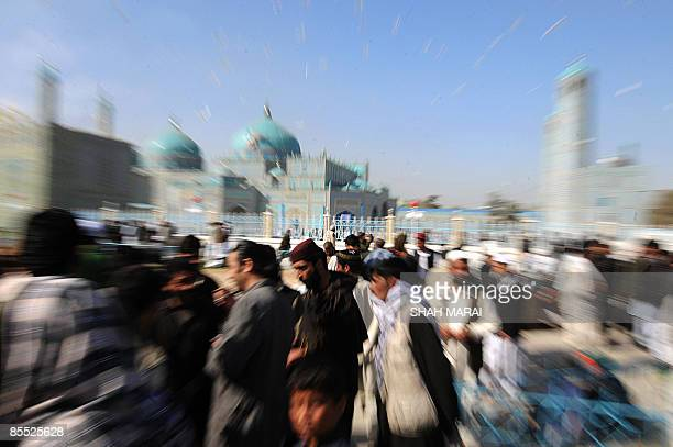 Afghan devotees walk at the Hazrat Ali Shrine in MazariSharif on March 20 2009 Tens of thousands of Afghans from all over the warscarred country have...