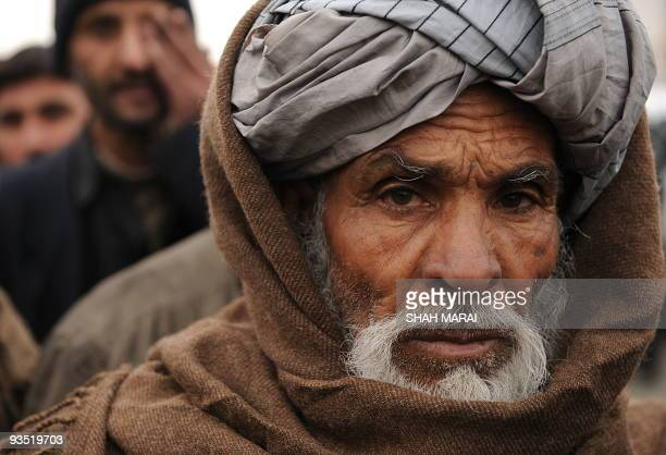 Afghan displaced men queue to receive aid during a distribution for the needy in Kabul on December 1 2009 As temperatures drop around the country the...