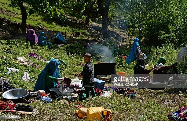Afghan displaced women wash their clothes outside near an area affected by landslides and flash floods in the GuzargaheNur district of the Baghlan...