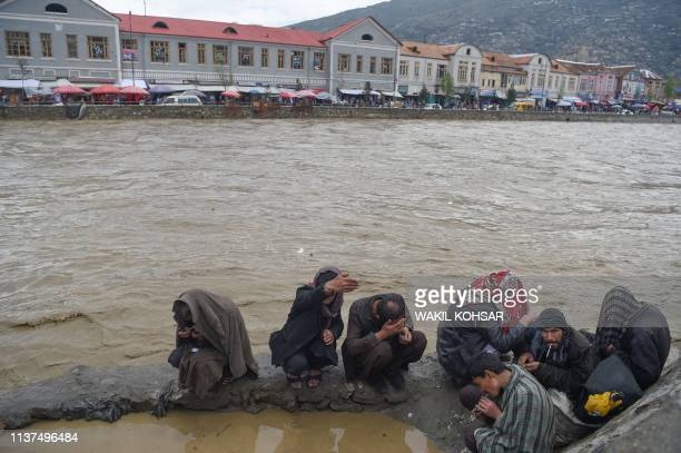 Afghan drug addicts smoke opium along the Kabul river after heavy rains in Kabul on April 16 2019 Torrential rainstorms have lashed droughtstricken...
