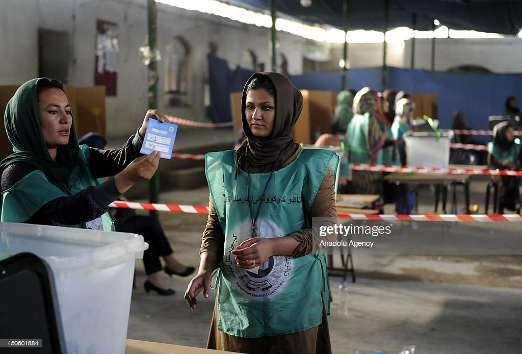 Afghan election officials count ballots at a polling station