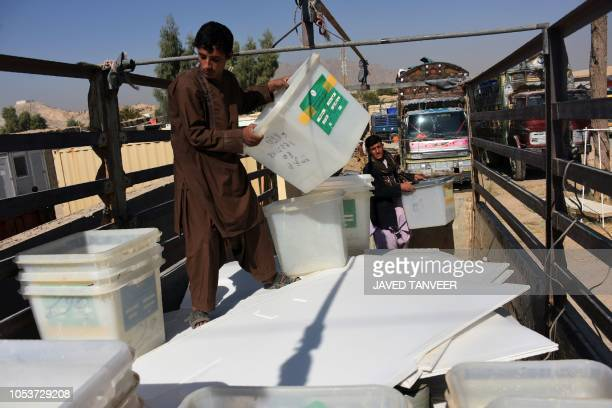 Afghan employees of the Independent Election Commission load ballot boxes onto a truck ahead of legislative election at a warehouse in Kandahar...