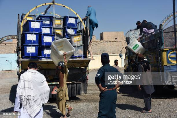 Afghan employees of the Independent Election Commission unload ballot boxes from a turck at a polling centre ahead of legislative election in...